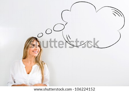 Pensive woman with a thought bubble and smiling - stock photo