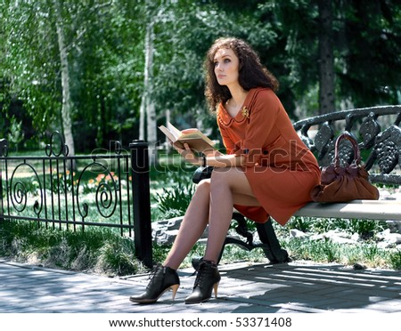 pensive woman with book on park bench