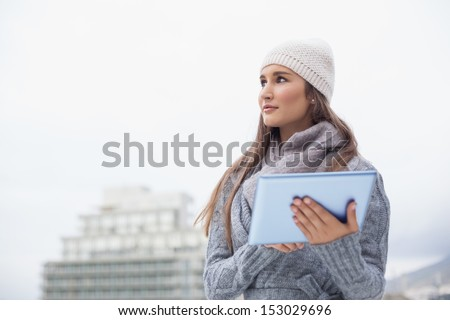 Pensive woman with winter clothes on using her tablet outdoors on a cold grey day - stock photo