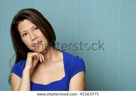 Pensive Young Asian Woman on Teal background