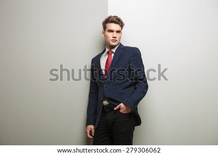 Pensive young business man holding one hand in his pocket while leaning on a grey wall. - stock photo