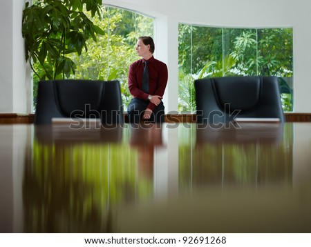 Pensive young business man looking out of the window in meeting room window. Front view, copy space - stock photo
