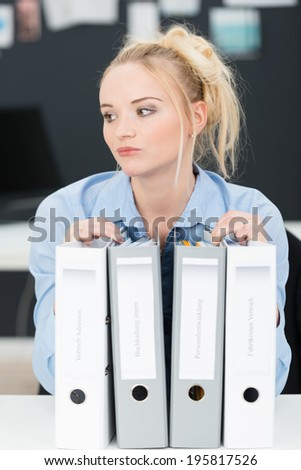 Pensive young businesswoman with a heavy workload and row of large files staring thoughtfully off to the side - stock photo