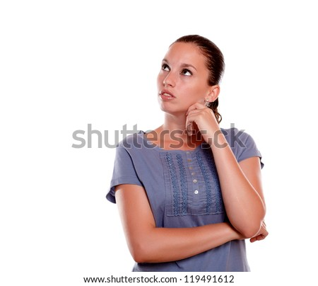 Pensive young female looking to her right up on blue shirt against white background - copyspace - stock photo
