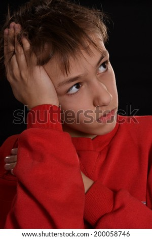 pensive young guy in a red shirt on a black background - stock photo