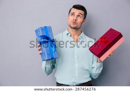 Pensive young man holding two gift box over gray background and looking up - stock photo