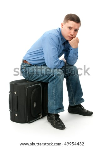 Pensive young man sitting on a hand bag. Isolated on white background - stock photo