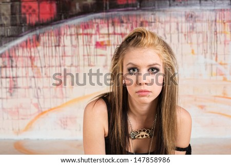 Pensive young white female teenager in urban scene - stock photo