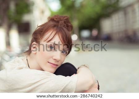 Pensive young woman gazing at the camera with a serious expression as she sits hugging her knees outdoors with copyspace - stock photo