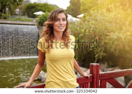 Pensive young woman in casual clothing standing near park waterfall - stock photo