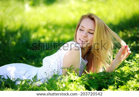 Pensive young woman lying in the green grass, enjoying summer sunny day - stock photo