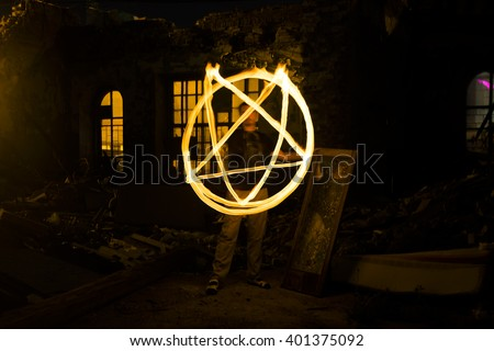 Pentagram made of fire flames . Man paint satan star from freezelighting at night time. Witch inside dark Castle or lock. Dusk light - stock photo