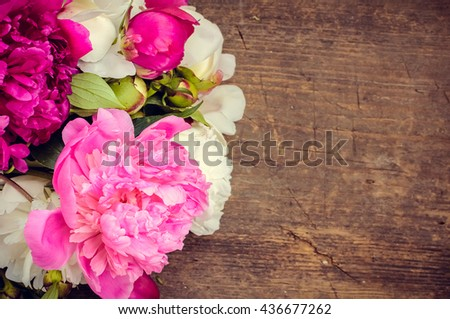 Peony background. Fuchsia, pink and white peonies on wooden table with place for text. Spring flower peony. Happy Mothers Day. Mother's Day greetings card. Mothers Day gift. Copy space. - stock photo