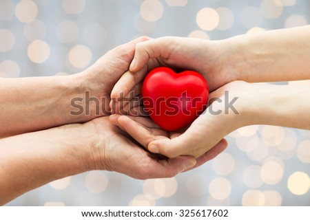 people, age, family, love and health care concept - close up of senior woman and young woman hands holding red heart over lights background - stock photo