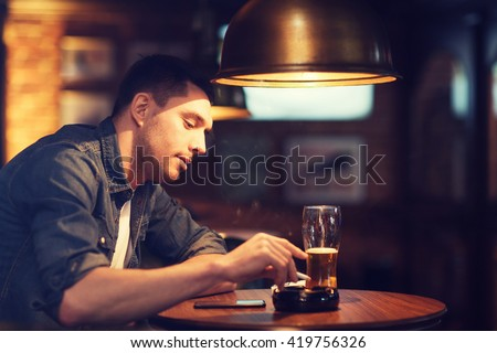 people and bad habits concept - man drinking beer and smoking and shaking off ashes of cigarette at bar or pub - stock photo