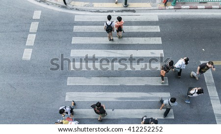 People and couple are walking across the crosswalk on top view (aerial photo) - stock photo