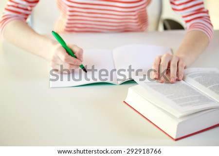 people and education concept - close up of female hands with book or textbook writing to notebook at school - stock photo