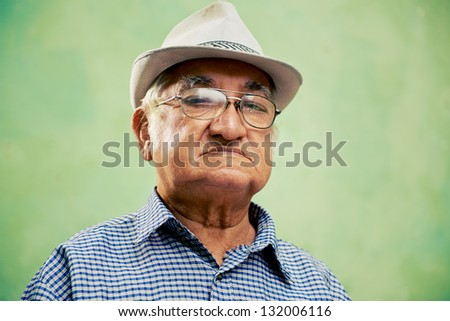 people and emotions, portrait of serious senior hispanic man with glasses and hat looking at camera against green background - stock photo