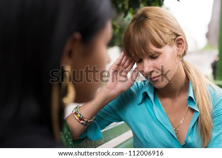 People and health, young woman feeling pain and talking with friend on bench - stock photo