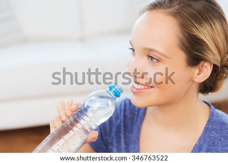 people and healthy lifestyle concept - happy woman with bottle of water at home - stock photo