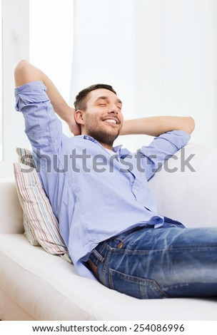 people and leisure concept - smiling man with closed eyes relaxing on couch at home - stock photo