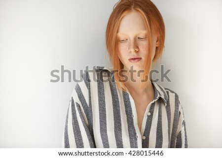 People and lifestyle concept. Close up shot of female student wearing striped pajamas at home in the morning before going to school. Pretty teenage girl with freckles and ginger hair looking down - stock photo