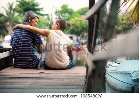 People and recreation, senior man and boy fishing together on lake - stock photo