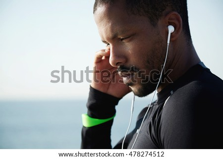 People and sport concept. Attractive young athlete in sportswear listening to his favourite tracks in headphones using smart phone, touching his head, thinking about his goals and achievements