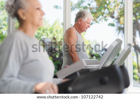 People and sports, elderly couple working out on treadmill in fitness gym - stock photo