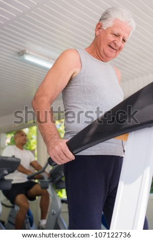 People and sports, elderly man working out on treadmill in fitness gym - stock photo