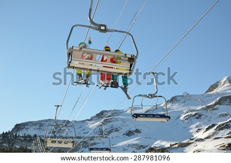 People are being transported with a chair lift up the snowy slope in the ski resort