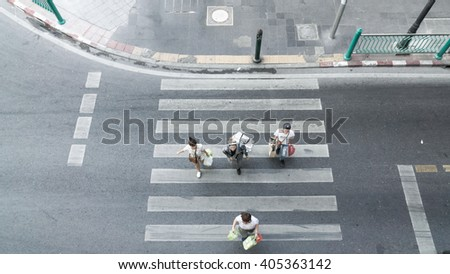 People are moving across the crosswalk on top view - stock photo