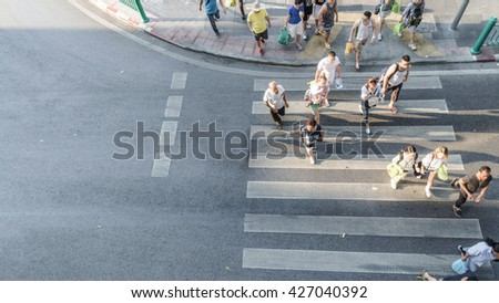 People are moving across the pedestrian crosswalk in the city road (on top view) - stock photo