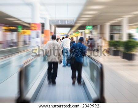 people are moving to their gates at the airport, motion effect. focus on the man in white shirt - stock photo