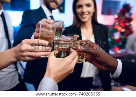 People are preparing to meet the new year in the office. They hold glasses with champagne. They are fun and they want to have a new year's party in the office.