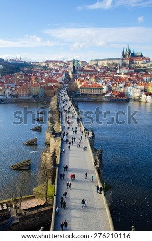 people are trying to cross charles bridge in prague in order to get to the famous prague castle, hradcany district and church of saint nicolas which are situated on the opposite shore of vltava - stock photo