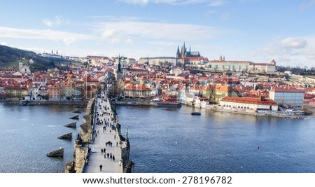 people are trying to cross charles bridge in prague in order to get to the famous prague castle, hradcany district and church of saint nicolas which are situated on the opposite shore of vltava