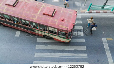 People are walking across road before the bus is going at the crosswalk in top view (aerial photo)  - stock photo