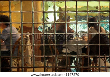 People at a restaurant seen through a glass block wall.