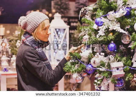 people at christmas market, woman choosing festive decoration in the shop