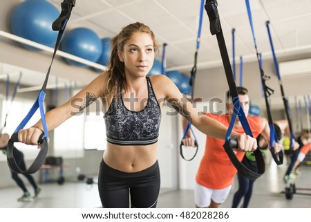 People at gym doing elastic rope exercises at cross fit room