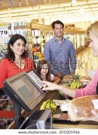 People at supermarket checkout - stock photo
