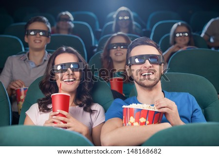 People at the cinema. Cheerful people in three-dimensional glasses watching movie at the cinema - stock photo