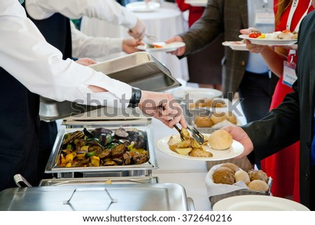 People at the reception taking food on plates - stock photo