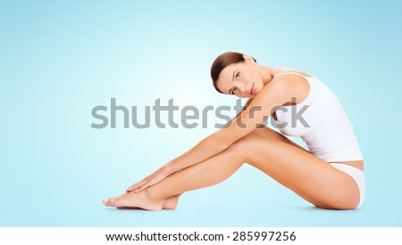 people, beauty and body care concept - beautiful woman in cotton underwear touching legs over blue background - stock photo