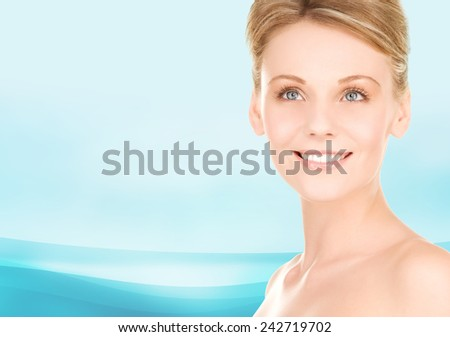 people, beauty and health care concept - close up of smiling young woman over blue background - stock photo