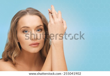 people, beauty, body and skin care concept - beautiful woman face and hands over blue background - stock photo