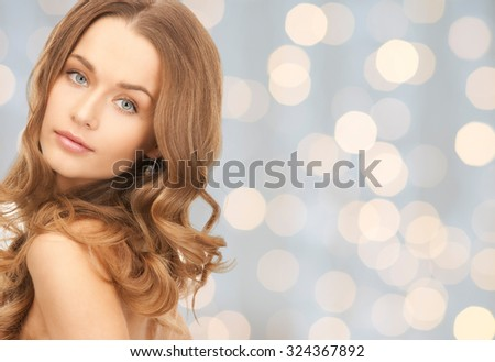 people, beauty, hair and skin care concept - beautiful woman with curly hairstyle over holidays lights background - stock photo