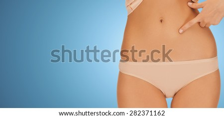 people, beauty, health and body care concept - close up of woman pointing finger at her abs over blue background - stock photo