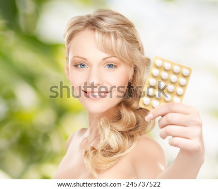 people, beauty, healthcare and medicine concept - happy young woman holding package of pills over green background - stock photo